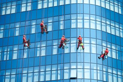 Fassadenreiniger reinigen die Glasfassade eines großen Bürogebäudes in München